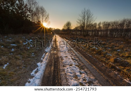 sunset over sandy road at winter - stock photo