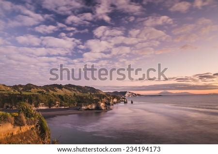 sunset over sea shore rocks and mount Taranaki New Zealand - stock photo