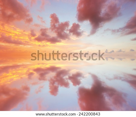 Sunset over sea with reflection in water - stock photo
