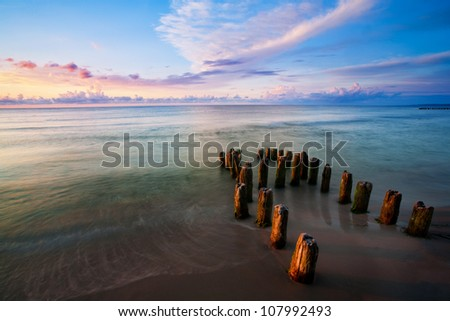 Sunset over the Baltic sea with a breakwater and beauty sky - stock photo