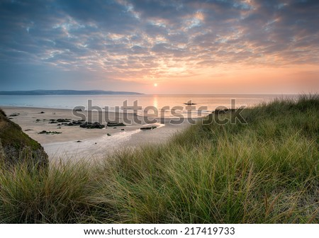 Sunset over the beach at Hayle in Cornwall from the sand dunes at Gwithian Towans - stock photo