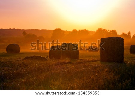 Sunset over the fields, and straw. - stock photo