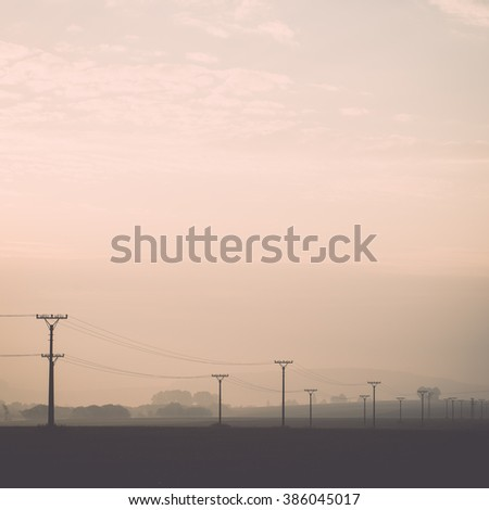 sunset over the fields in fog in summer with electricity poles - vintage effect - stock photo