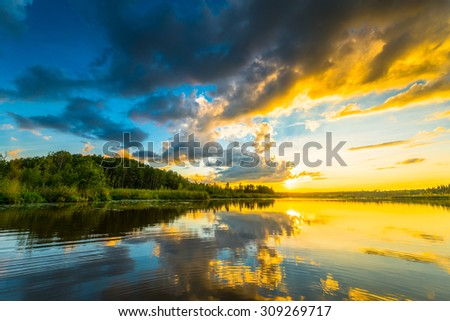 Sunset over the forest lake. View from the boat - stock photo