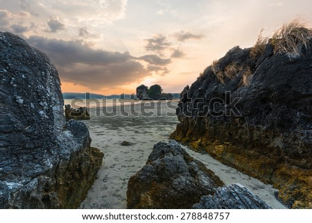 sunset over the giant rock on the beach - stock photo