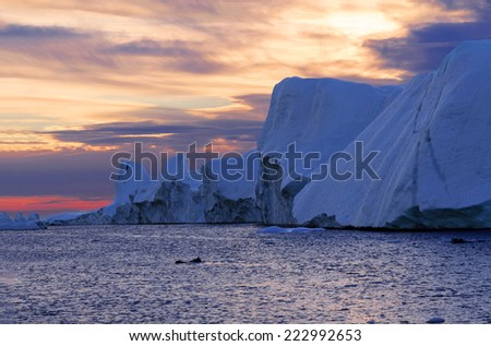Sunset over the Icefjord, Greenland. Ilulissat Icefjord is a fjord in western Greenland and was declared a UNESCO World Heritage Site in 2004.  - stock photo