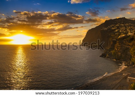 Sunset over the island of Madeira. The town on the right is called Camara de Lobos. - stock photo