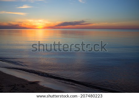 Sunset over the Lake Huron horizon. Port Crescent State Park. Port Austin, Michigan.  - stock photo