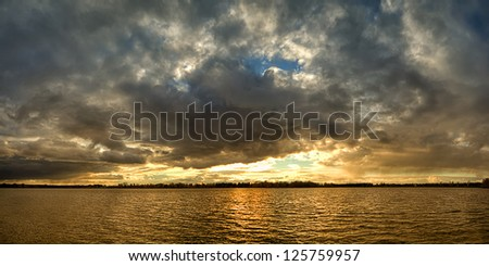sunset over the lake, the sunset over the water, evening sunset, the sky at sunset, the clouds at sunset, sunset over the cloudy sky, - stock photo