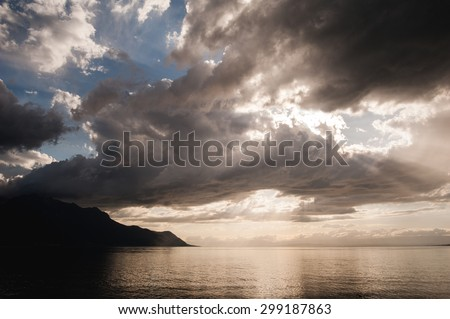 sunset over the lake, the sunset over the water, evening sunset, the sky at sunset, the clouds at sunset, sunset over the cloudy sky, geneva lake  - stock photo