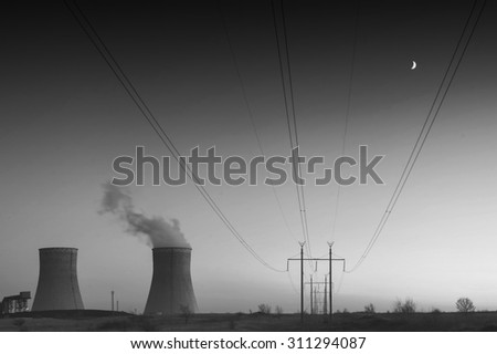 Sunset over the nuclear power plant. Black and white - stock photo