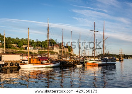 Sunset over the Oslo harbor with many old wooden sail boats and the Akershus Fortress in the background in Norway capital city. - stock photo