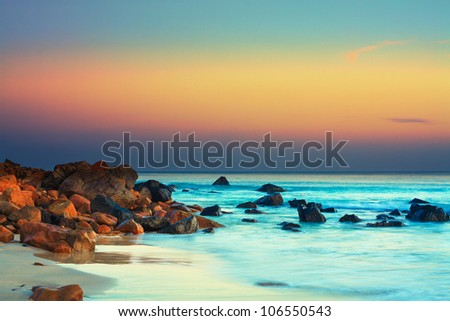 Sunset over the sea. Stone on the foreground - stock photo