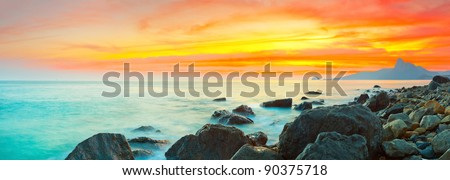 Sunset over the sea. Stone on the foreground. Panorama - stock photo