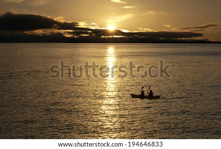 Sunset over the sea with boat - canoe - stock photo