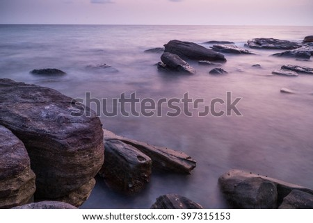 sunset over the sea with rocks and stone in foreground. purple color atmosphere with long exposure speed shutter. evening time - stock photo