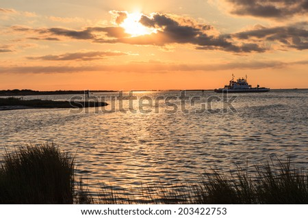 Sunset over the water route of ferry boats connecting Hatteras Island with Ocracoke in the Outer Banks of North Carolina. - stock photo
