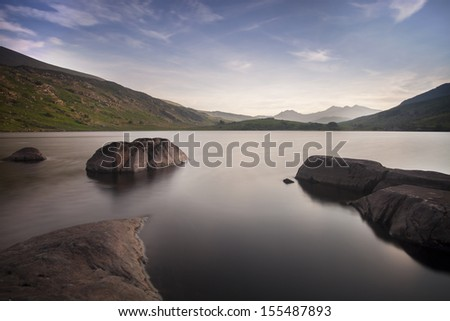 sunset overlooking peaceful lake side scene in snowdonia, north wales - stock photo