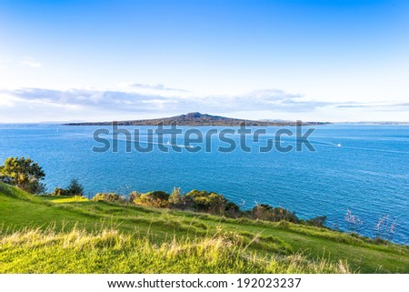 Sunset pacific landscape with a volcano on a horizon. Rangitoto island in Hauraki gulf, view from Devonport, Auckland. New Zealand. - stock photo