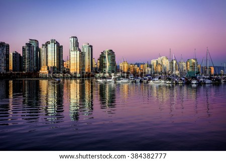 Sunset partially illuminates the glass buildings on the waterfront, with boats on the right - stock photo
