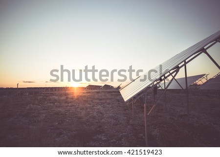 Sunset rays over a photovoltaic power plant.Background of photovoltaic modules for renewable energy.Power plant using renewable solar energy with sun - stock photo