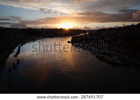 Sunset reflected on Douro river waters, between Porto nd Gaia in Portugal. - stock photo
