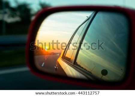 Sunset reflection in the rear view mirror of a car on a highway. Blur shot - stock photo