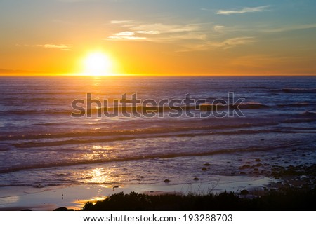 Sunset reflects off waves on California coast - stock photo