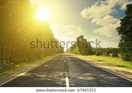 Sunset road in russian hills. Yellow sunbeams. Rural scene. - stock photo