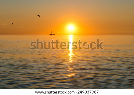 sunset - sailing ship silhouette on the sunset background - stock photo
