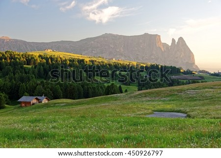 Sunset scenery of beautiful alpine mountains with view of Schlern mountain peaks in background, farmhouses on hills under golden sunlight & green grassy meadows in seiser alm, Dolomiti, Italy, Europe - stock photo