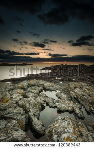 Sunset seascape from Trearddur Bay on the island of Anglesey in North Wales. The sky is reflected in the rock pools and the jagged rock that makes up this reef is some of the oldest on the planet. - stock photo