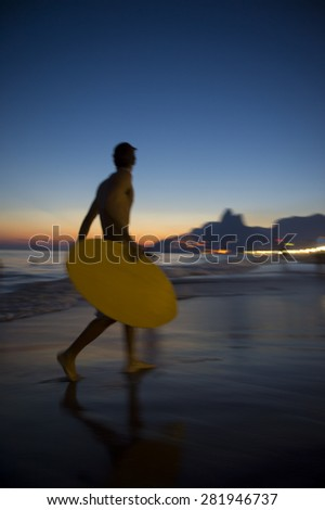 Sunset silhouette of Brazilian holding skimboard on Ipanema Beach Rio de Janeiro Brazil  - stock photo