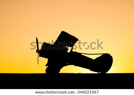 sunset silhouette of old bi plane - stock photo