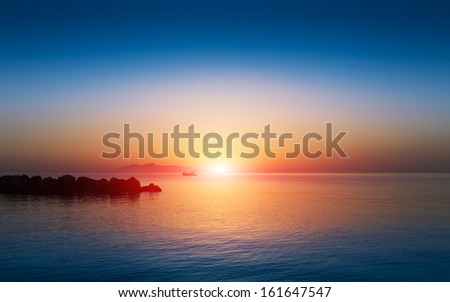 Sunset sky in the Aegean sea with boat and mountains, Santorini - stock photo