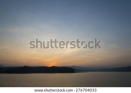 sunset sky over lake in Kanchanaburi, Thailand. - stock photo