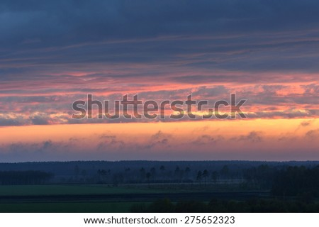 Sunset sky with clouds, fields and forest - stock photo