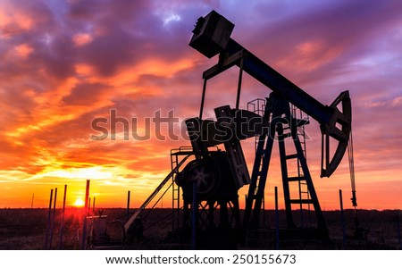Sunset sky with profiled oil and gas well pump - stock photo