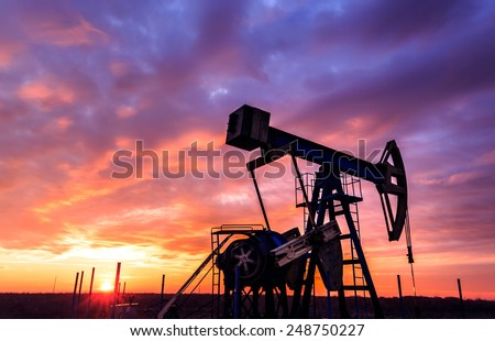 Sunset sky with profiled oil well - stock photo