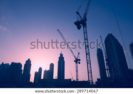 Sunset skyline of construction cranes amongst office tower skyscrapers in the Middle East center of trade, Dubai - stock photo