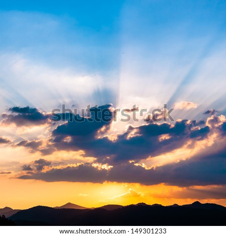 Sunset / sunrise with clouds, light rays and other atmospheric effect over the hills and mountains in Slovenia, Europe. - stock photo
