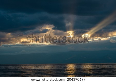 sunset through the clouds over the sea - stock photo