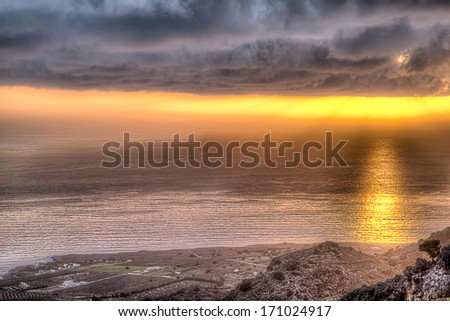 Sunset throwing a glowing pathway across the sea as it shines from behind a heavy bank of cloud turning the horizon a vivid orange - stock photo