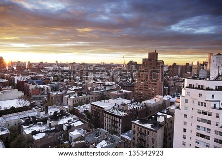 Sunset time over the West Village (Greenwich Street) in a New-York Winter, with snow residue on the rooftops. - stock photo