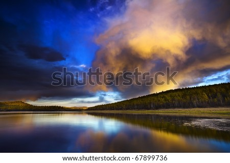 Sunset under the lake and forest - stock photo