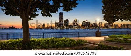 Sunset view from Manhattan of Jersey City and Hudson River waterfront with skyscrapers. - stock photo