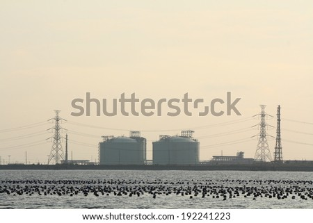 sunset view of factory near the sea - stock photo
