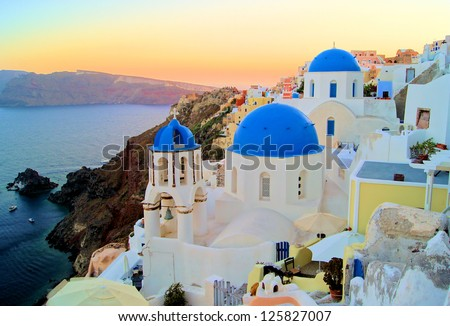Sunset view of the blue dome churches of Santorini, Greece - stock photo