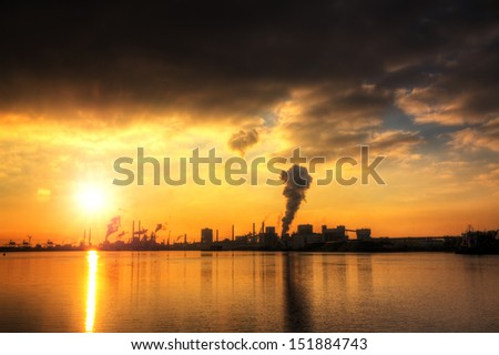Sunset view of the heavy industry with smoking chimneys in IJmuiden, the Netherlands - stock photo