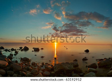 Sunset view over Baltic sea with stones - stock photo
